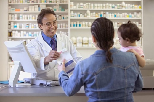 Stock Photo: 1589R-03272 Pharmacist giving medication to a mid adult woman