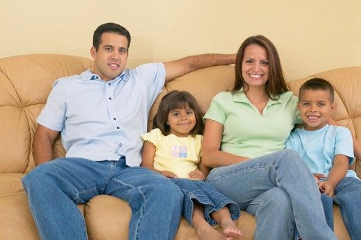 Stock Photo: 1589R-03667 Portrait of a young couple sitting with their children on a couch