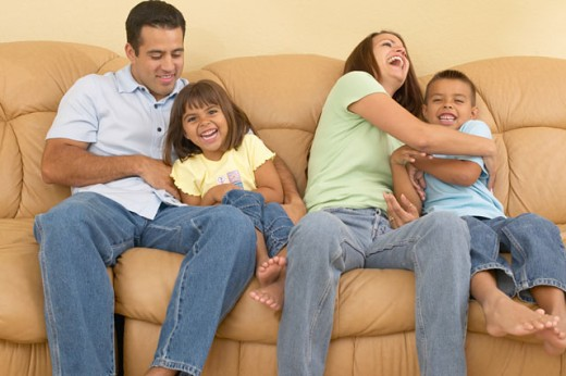 Young couple playing with their children on a couch : Stock Photo