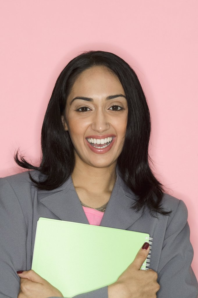 Portrait of a businesswoman holding a file smiling : Stock Photo