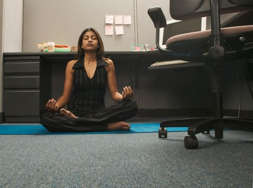 Stock Photo: 1589R-04181 Portrait of a young woman meditating on the floor of an office