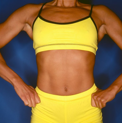 Close-up of a the torso of a muscular young woman : Stock Photo
