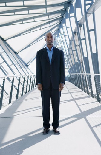 Businessman standing on a walk bridge : Stock Photo
