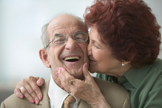 Portrait of a senior woman kissing a senior man on the cheek : Stock Photo