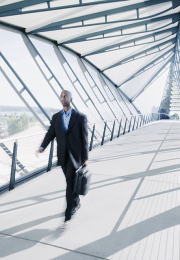 Stock Photo: 1589R-0429 Businessman walking carrying a briefcase on a walk bridge