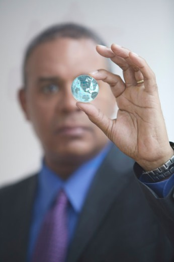 Stock Photo: 1589R-04294 Businessman holding a glass globe