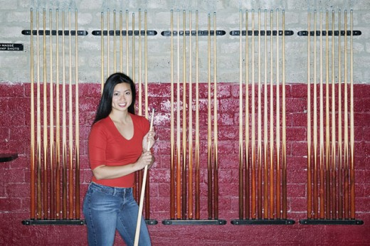 Stock Photo: 1589R-0452 Young woman standing holding a cue stick in front of a wall of racks of cue sticks