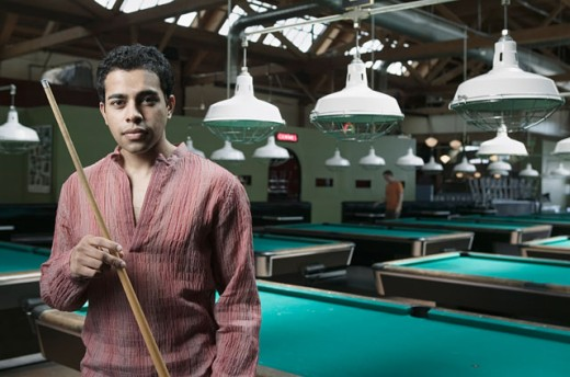 Man holding pool a cue stick standing in a pool hall : Stock Photo