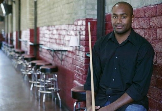 Stock Photo: 1589R-0460 Man holding a pool stick standing in a pool hall