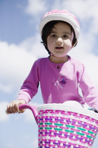 Stock Photo: 1589R-04730 Low angle view of a young girl riding a bicycle wearing a helmet
