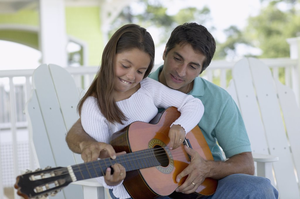 Young man teaching a young girl to play the guitar : Stock Photo