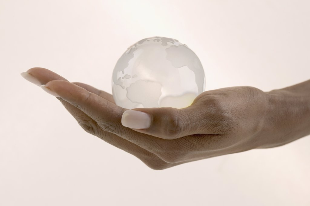 Stock Photo: 1589R-05121 Woman's hand holding a glass globe in the palm of her