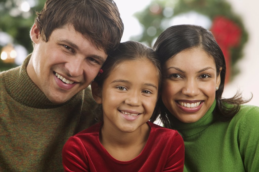 Young couple and their child looking at camera smiling with a Christmas tree in the background : Stock Photo