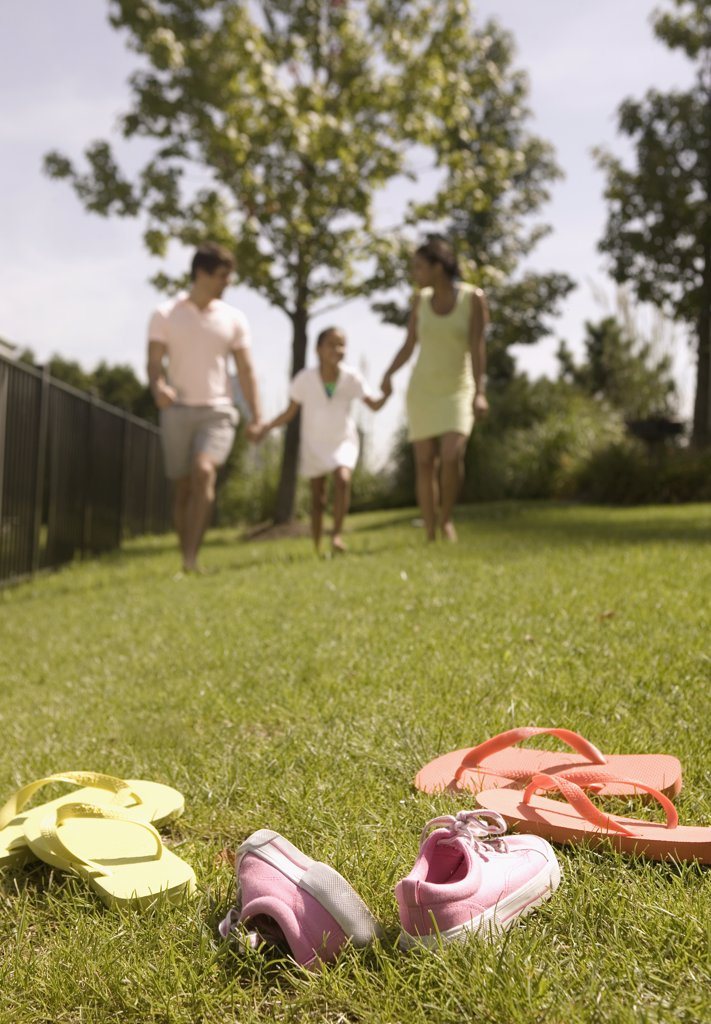 Stock Photo: 1589R-05195 Low angle view of a young couple and their child running on a lawn