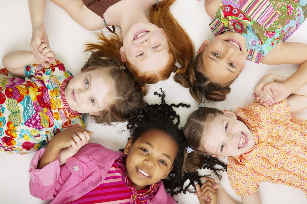Stock Photo: 1589R-05215 High angle view of a group of young girls lying down together smiling