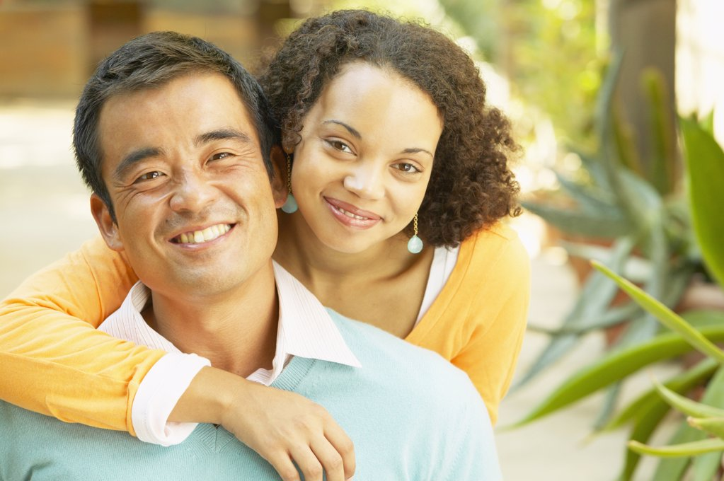 Stock Photo: 1589R-05424 Portrait of a young woman holding a mid adult man