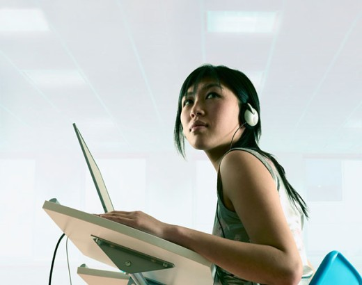 Stock Photo: 1589R-0576 Young woman operating laptop