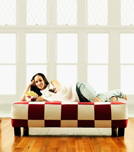 Stock Photo: 1589R-0580 Portrait of a young woman lying on couch