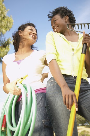 Stock Photo: 1589R-05836 Two Young women looking at each other smiling holding a garden hose and a rake