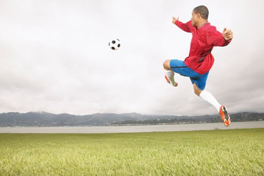 Young male football player in mid air : Stock Photo