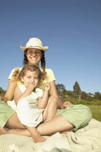 Portrait of a young woman sitting with a young girl : Stock Photo