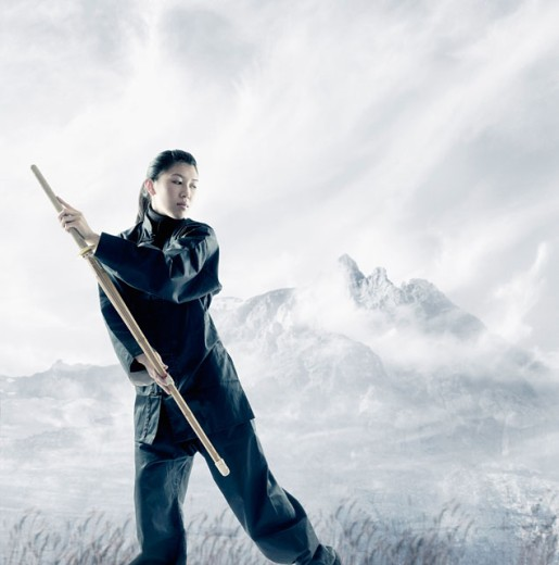 Stock Photo: 1589R-0593 Portrait of a young woman holding a wooden stick standing in a martial arts stance