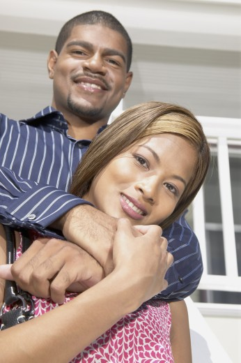 Young couple holding each other standing on stairs to a house : Stock Photo
