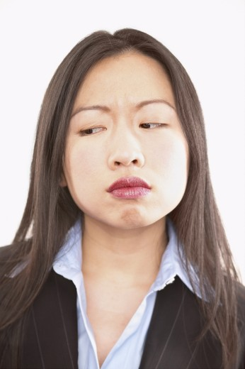 Portrait of a young businesswoman frowning : Stock Photo