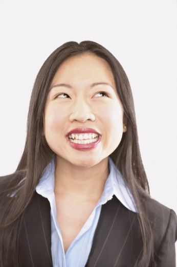 Portrait of a young businesswoman looking up smiling : Stock Photo
