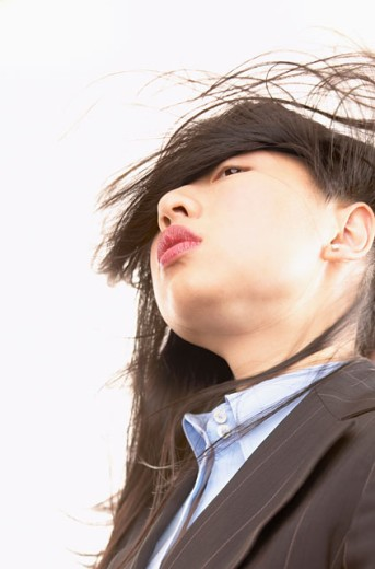Low angle view of a young businesswoman with her hair over her face : Stock Photo