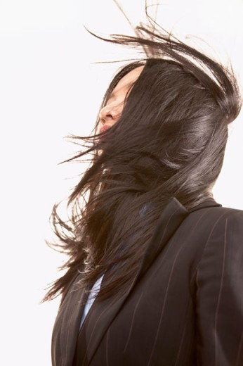 Low angle view of a young businesswoman with her hair blowing over her face : Stock Photo