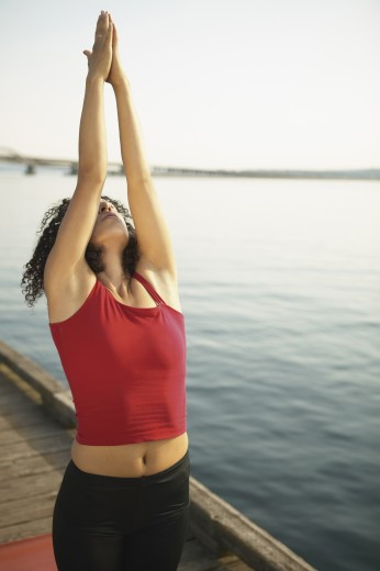 Young woman performing yoga outdoors : Stock Photo