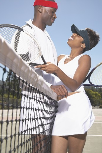 Stock Photo: 1589R-06325 Young couple holding tennis rackets standing on a tennis court