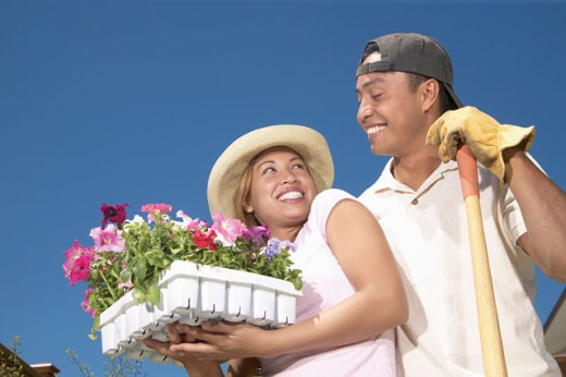 Stock Photo: 1589R-06381 Young couple standing together in a garden holding potted plants smiling