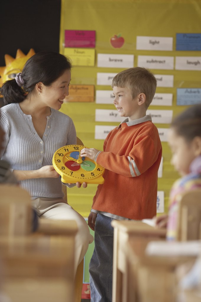 Female teacher and her student holding a clock in a classroom : Stock Photo