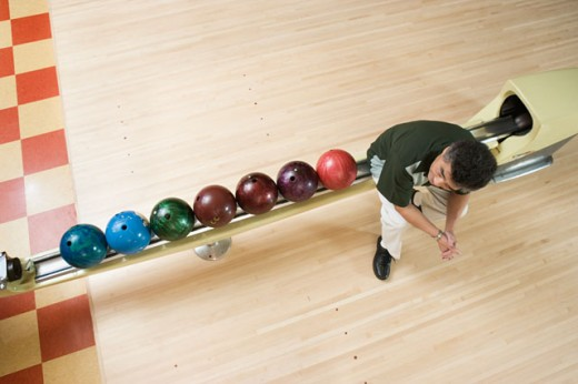 High angle view of a mature man sitting on a channel in a bowling alley : Stock Photo