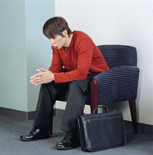 Businessman sitting on an arm chair : Stock Photo