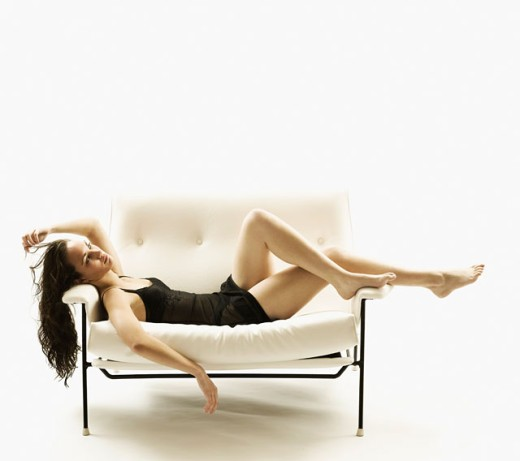 Young woman lying on a couch : Stock Photo