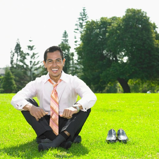 Stock Photo: 1589R-07282 Businessman sitting in a garden and laughing