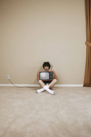 Portrait of a young man holding television : Stock Photo