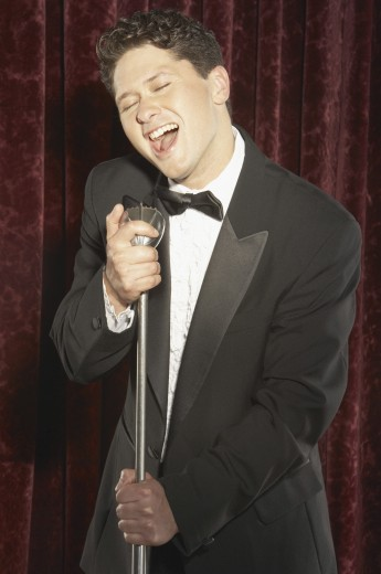 Young man holding a microphone and singing : Stock Photo