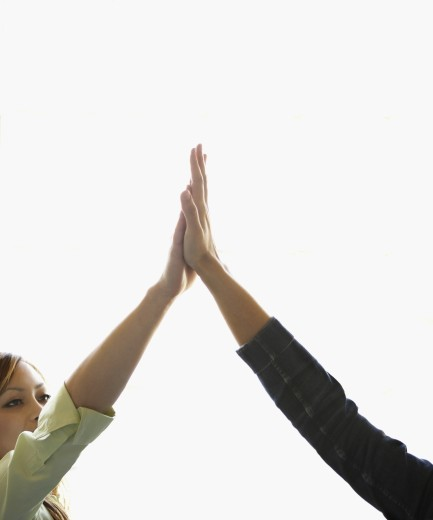 Stock Photo: 1589R-07597 Two young women giving high-five