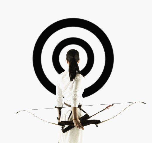 Rear view of a young woman holding a crossbow looking at a target : Stock Photo