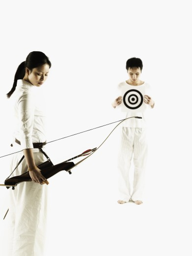 Stock Photo: 1589R-0789 Young woman holding a crossbow with a young man holding a target