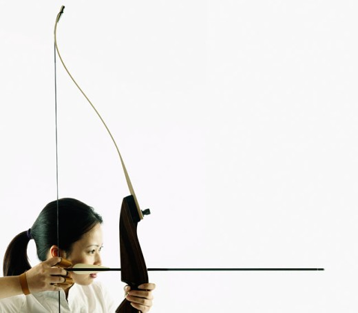 Stock Photo: 1589R-0790 Young woman aiming a crossbow