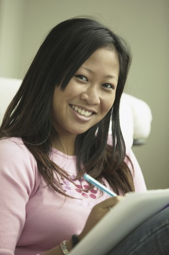Portrait of a teenage girl writing on a paper : Stock Photo