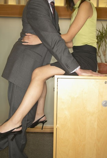 Businessman and a businesswoman flirting in an office : Stock Photo
