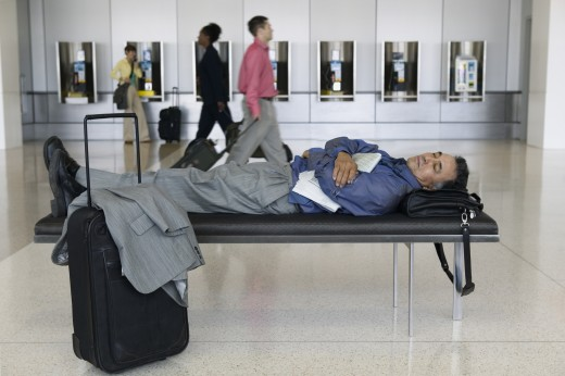 Side profile of a businessman sleeping on a bench in an airport lounge : Stock Photo
