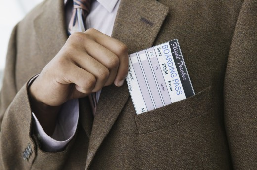 Stock Photo: 1589R-0922 Closeup of a businessman's hand removing a boarding pass from a jacket pocket