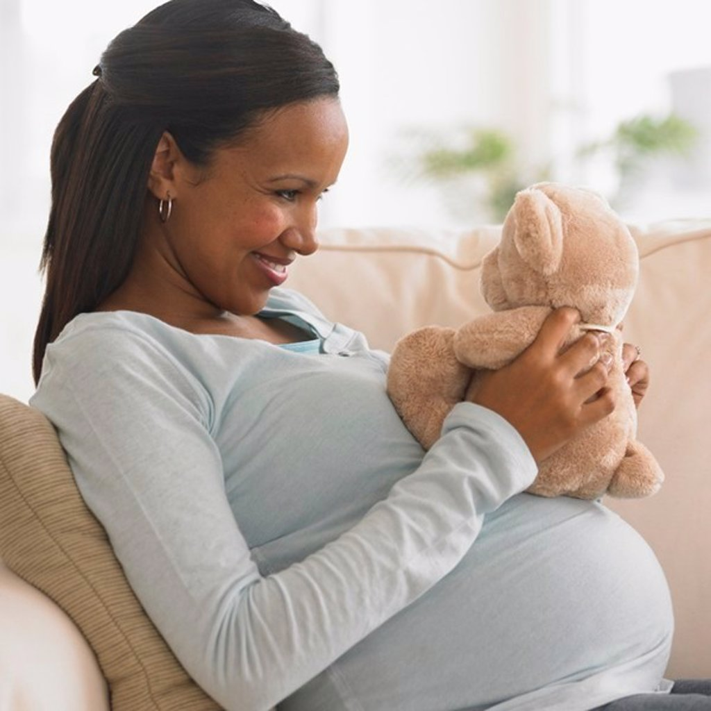 Stock Photo: 1589R-100548 Pregnant African woman hugging teddy bear
